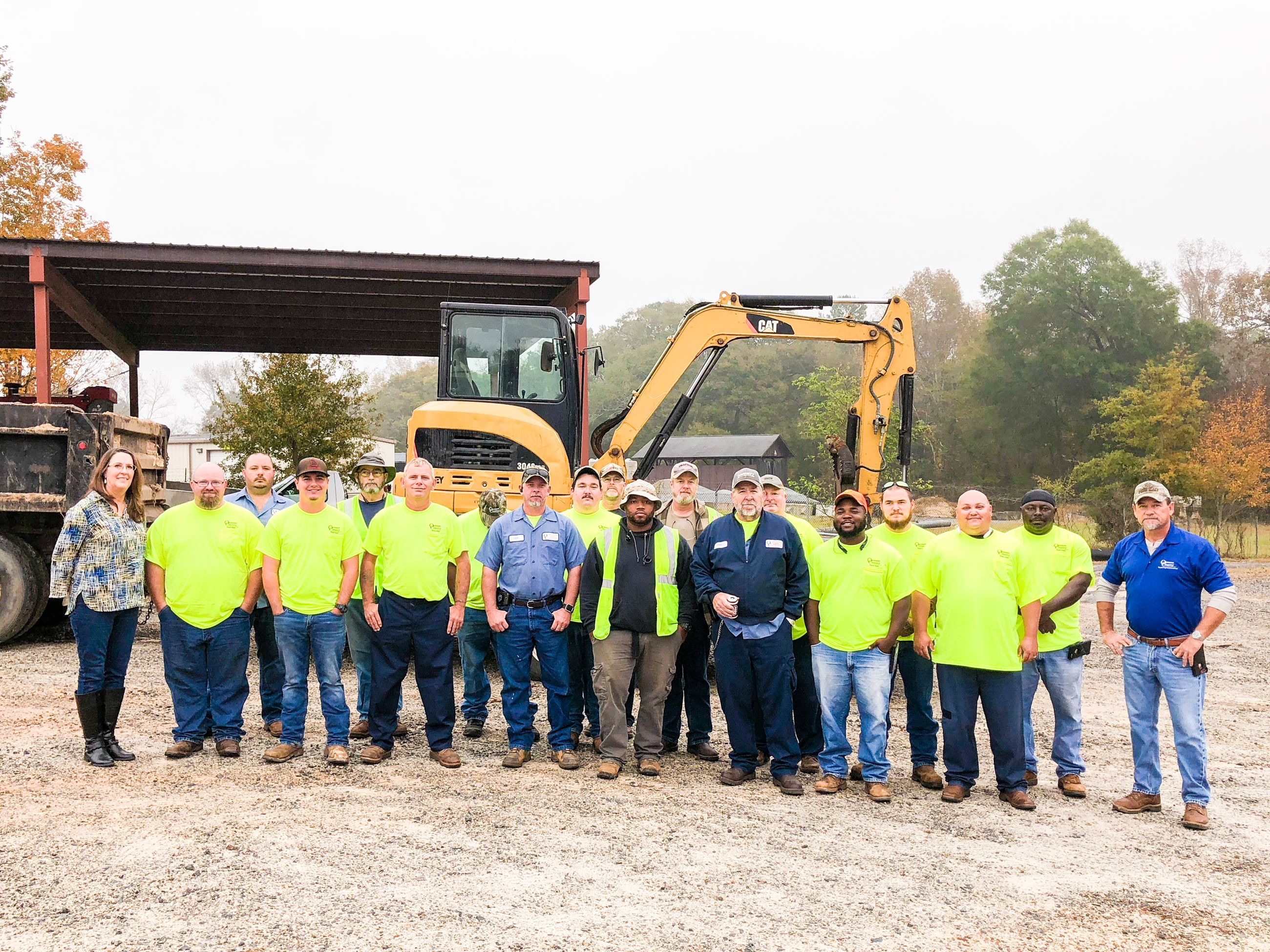 Photo of Road Department Staff Standing in Front of Road Equipment